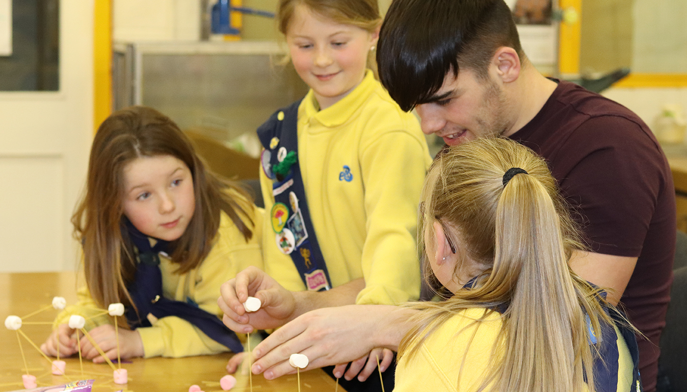 Fourth Year student Cormac Daly working with Naomh Bhuite Brownies on their STEM Engineering challenges